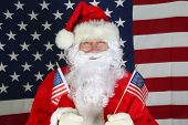 Santa Claus with American Flag. Santa stands in front of the American Flag while holding two smaller poster