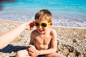 A Boy In Sunglasses Plays With His Mother On The Beach. Portrait Of A Laughing Child. Smiling Baby S poster