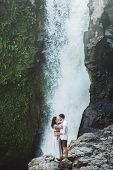 Man And Woman Romantic Kissing With Amazing View Of Tegenungan Cascade Waterfall. Happy Together, Ho poster
