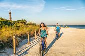 Biking couple cycling on florida beach tourists riding bikes in Sanibel island, Gulf of Mexico. Peop poster