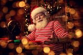 Santa Claus is preparing for Christmas at his wooden home - he sews gifts on a sewing machine. Santa poster