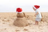 Little Child In Red Santa Hat With Sand Snowman On Beach. poster
