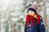 Adorable Young Girl Having Fun In Beautiful Winter Park During Snowfall. Cute Child Playing In A Sno poster