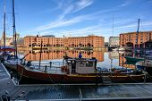 Wide Shot Across The Albert Dock In Liverpool With Boats Moored Around The Edges And Reflected In Th poster