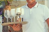 Hand Of Waiter Is Holding A Tray With Dirty Dishes And Empty Glasses. Waiter Cleaning The Table In A poster