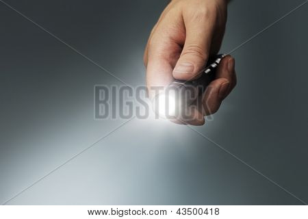 Man holding a small but powerful led flashlight in his hand.