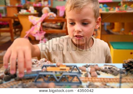 Boy Plays With Toy Railroad In Playroom