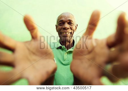 Old African Man With Hands And Arms Open, Embracing The Camera