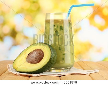 Useful fresh avocado and half avocado on wooden table on natural background