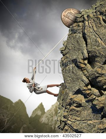 businesswoman climbing mountain with cent on top