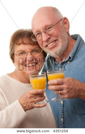Happy Senior Couple With Glasses Of Orange Juice