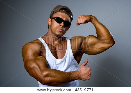 A Strong Man In Sunglasses Shows His Muscles. Trained Body.