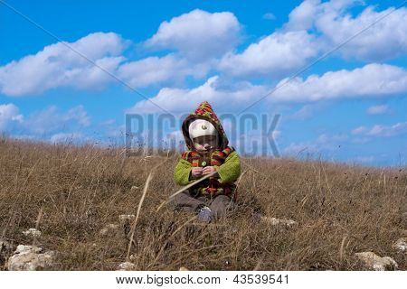 Baby sitting on a background of the sky in the steppe