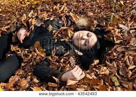 Woman Lying In Fallen Leaves
