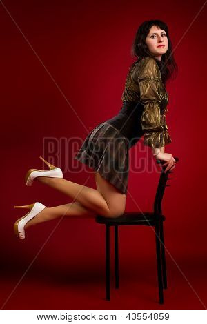 Young Brunette Woman Sitting On A Chair