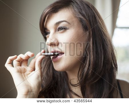 Beautiful Young Woman Eats Piece Of Dark Chocolate