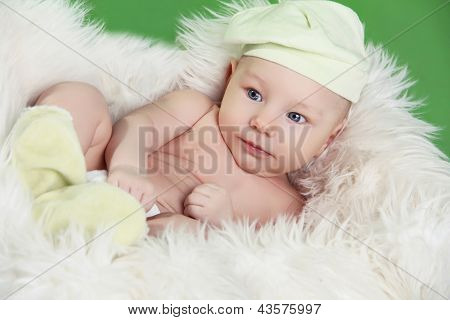 Portrait Of Funny Baby Boy Resting On Fur White Bed