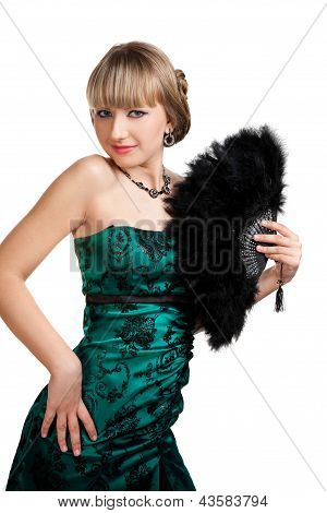 Beautiful girl in green evening dress with necklace and earrings hodling fan