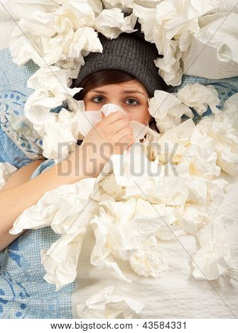 The Young Girl Is Lying Sick In Bed And Blowing Her Nose
