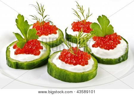 Red Caviar On A Green Cucumber Over White