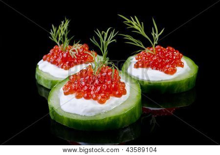 Red Caviar On A Green Cucumber, Isolated Over Black