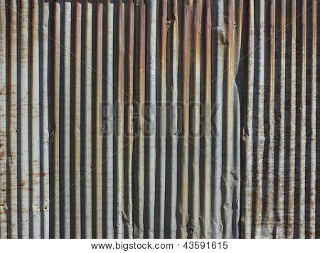 A rusty corrugated iron metal fence close up/ Zinc wall