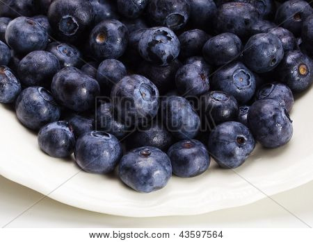 Ripe blueberries in a pile on tan counter top and brown background