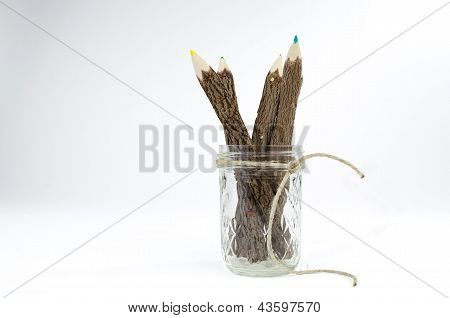 Group of multicolored bark covered tree branch pencils in glass mason canning jar with hemp rope twi