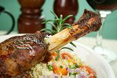 stock photo of lamb shanks  - Roasted lamb shank on tomato butternut pumpkin and parsley couscous.