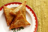stock photo of samosa  - Curry mince samosas on a white and red plate - JPG