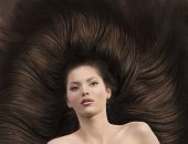 stock photo of nack  - pretty brunette lying on her long brown hair laying down she looks in to the lens with nacked shoulders - JPG
