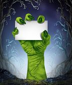 pic of creepy  - Zombie rising hand holding a blank sign card as a spooky halloween or scary symbol with textured green skin and monster fingers with stitches in a foggy night time tree forest background as a cemetary like creepy place - JPG