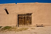 Adobe Building With Old Door And Bench