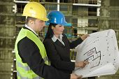 stock photo of engineering construction  - Engineer and client looking on project on the construction site - JPG