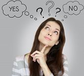 foto of finger  - Thinking young woman with yes or no choice looking up with finger at face on grey background - JPG