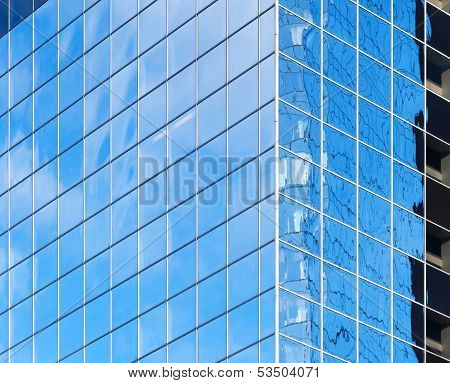 Corner Of Modern Office Building With Bright Blue Sky Reflections In Windows