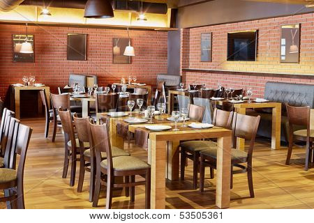 Restaurant room with wooden furniture and walls of red bricks
