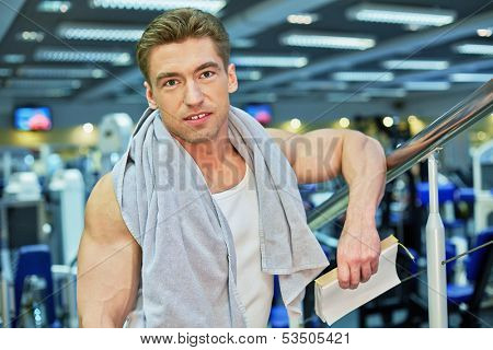 Portrait of smiling bodybuilder who stands with towel on his shoulders and scratchpad in hand