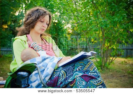 Mother Breastfeeding While Reading The Book