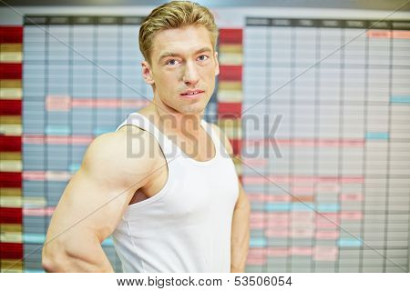 Half-length portrait of bodybuilder who stands half-turned with his arms akimbo against training schedule