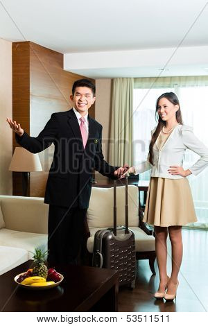 Asian Chinese Hotel Manager or director or supervisor presenting arriving VIP guests the room or suite