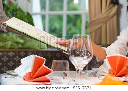 Woman In A Restaurant Choosing Meal From Menu