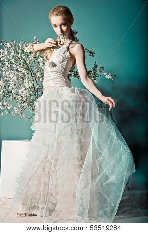 Bride in wedding dress behind bush with flowers
