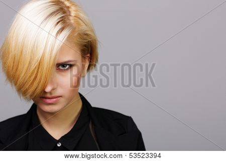 closeup portait of a young vicious woman on gray background