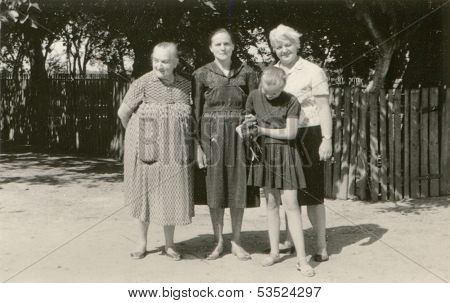 Vintage photo of two grandmothers, mother and daughter with a chicken on farm, fifties