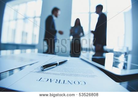 Close-up of business contract with pen at workplace on background of office workers interacting