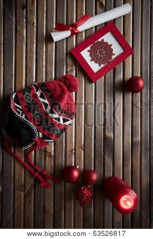Image of red snowflake in frame, decorative toy balls, cap, burning candle and rolled paper wrapped with red silk ribbon on wooden background
