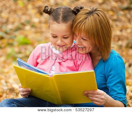 Mother is reading book with her daughter, outdoor shoot