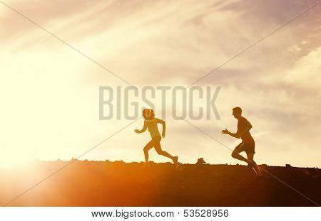 Silueta de hombre y mujer corriendo juntos en puesta de sol, concepto de fitness Wellness