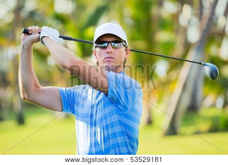 Athletic young man playing golf, Golfer hitting fairway shot, swinging club